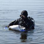 Nurek wyciąga śmieci z dna jeziora Lubie